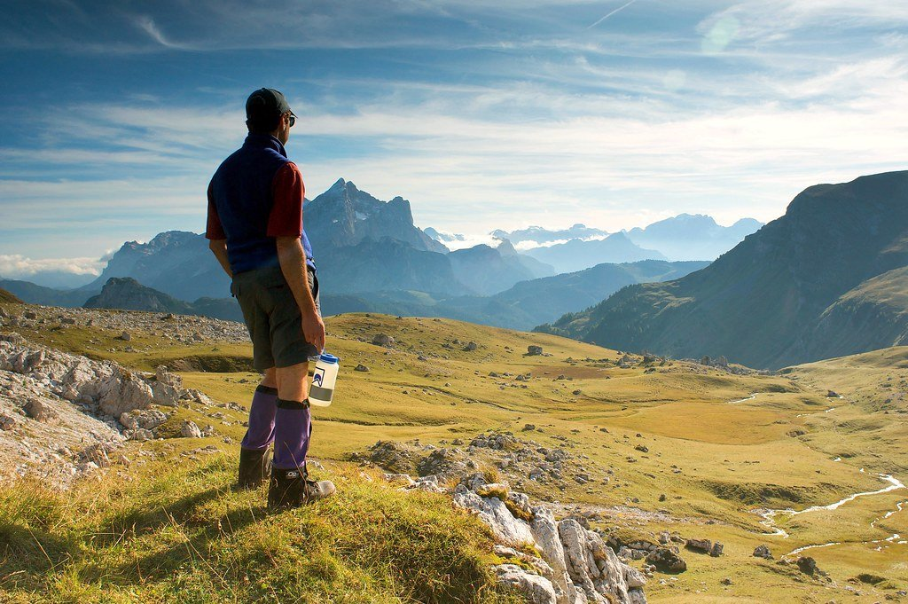 man wearing hiking gear and holding water bottle looks out over a green valley toward rugged mountains