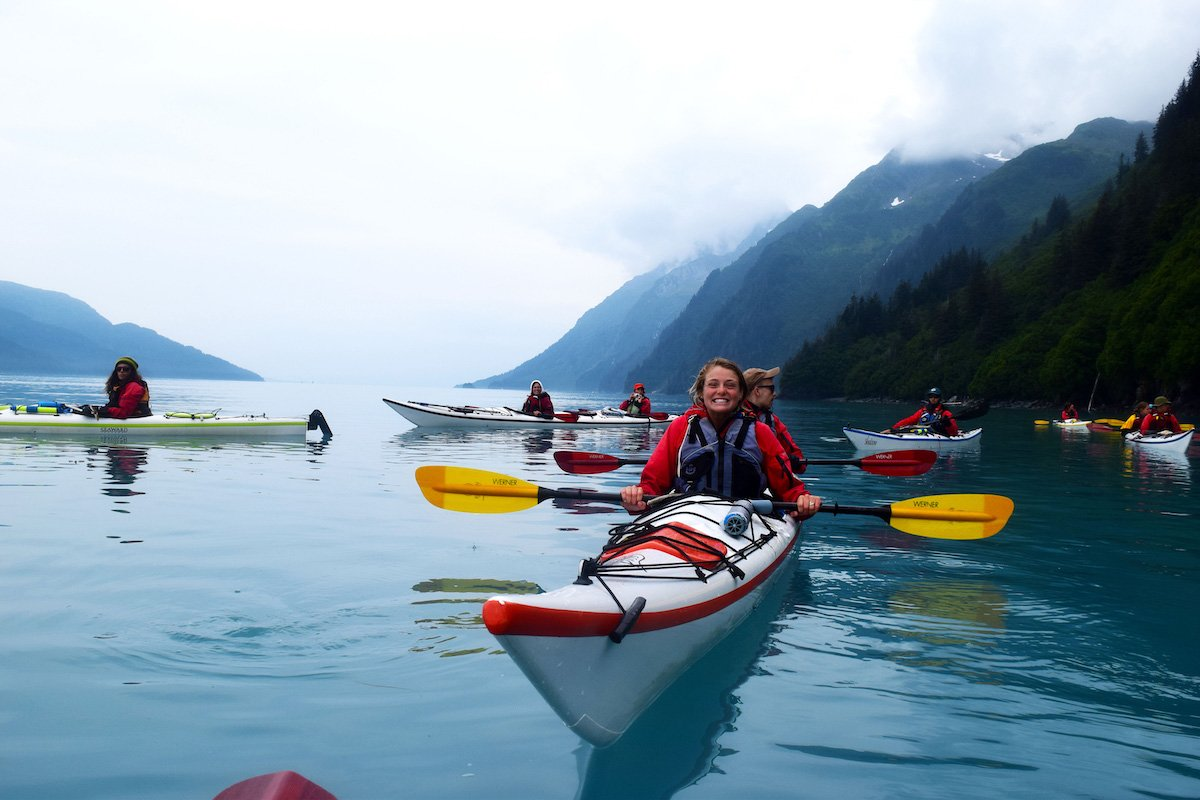 smiling NOLS students paddle single and double kayaks on calm water on a foggy day in Alaska