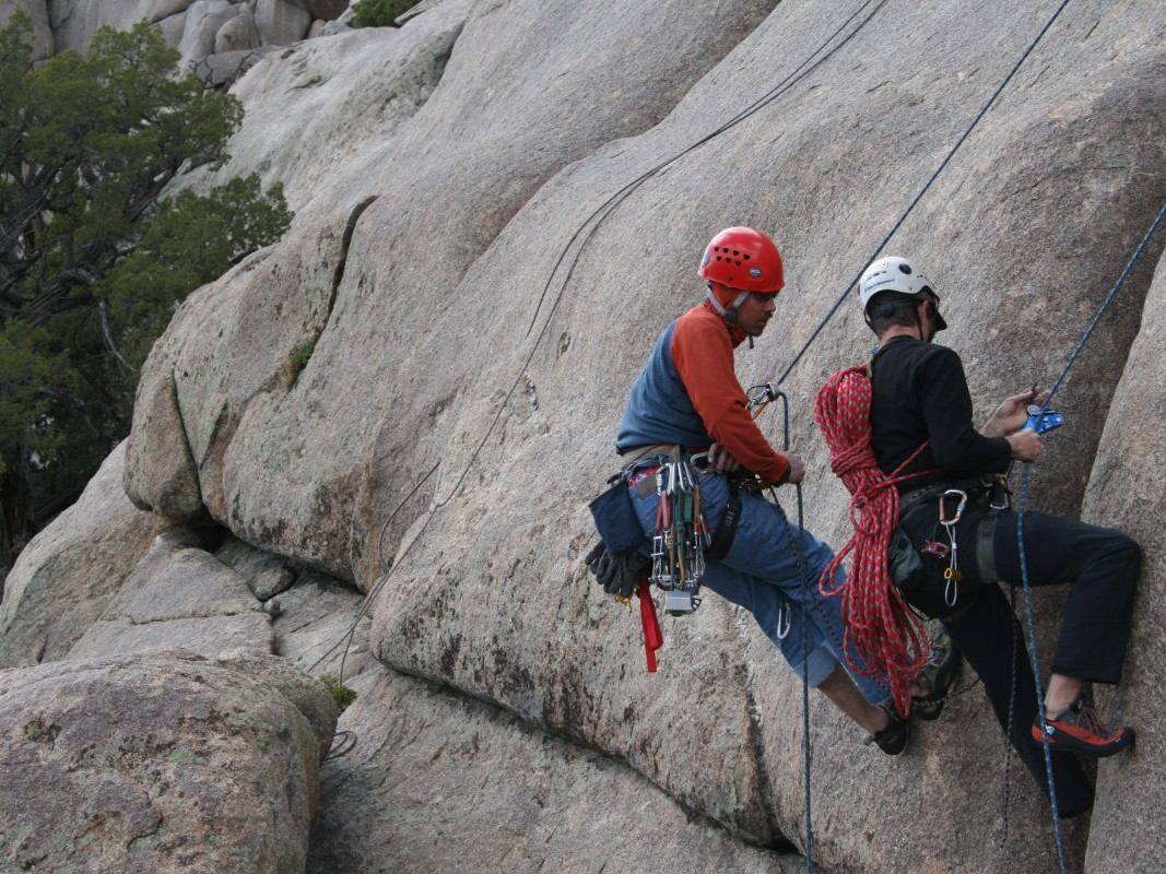 One person coaches another down a rock face