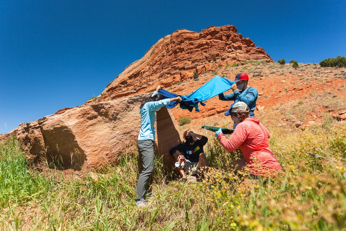 People provide shade for a patient in a practice wilderness medicine scenario