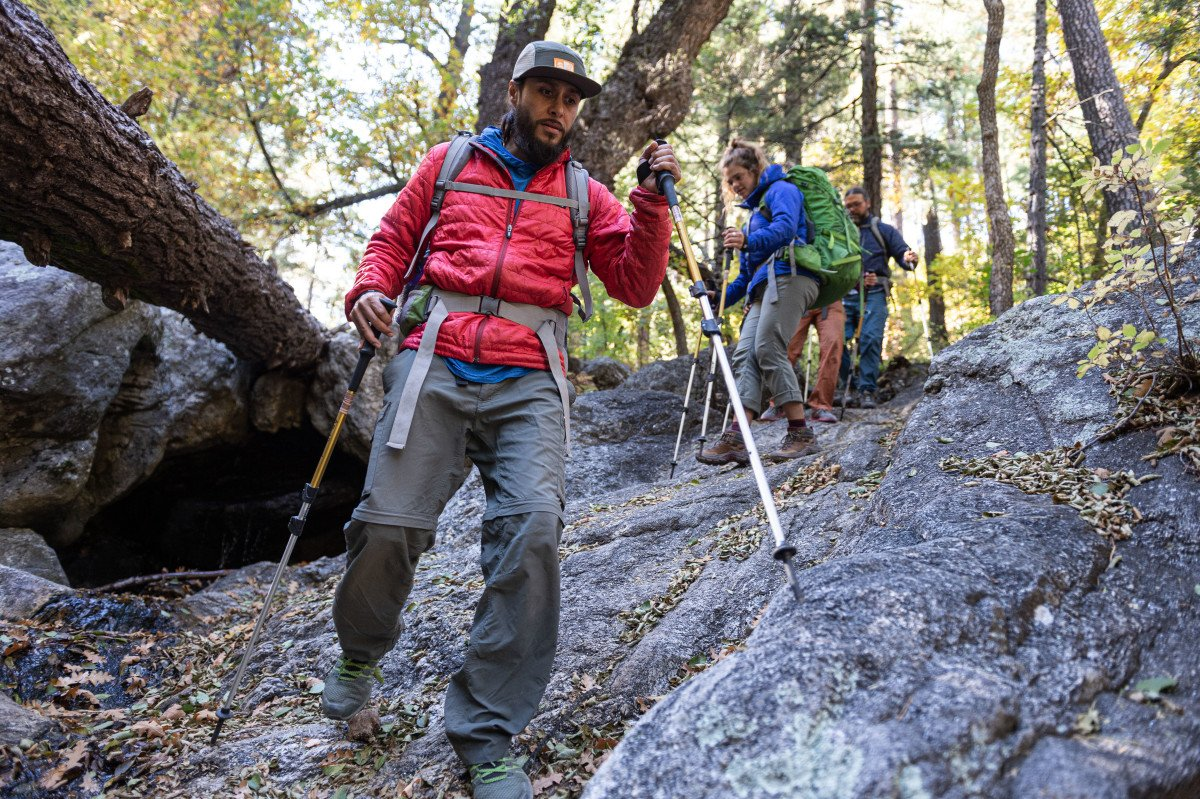 People hiking downhill with trekking poles