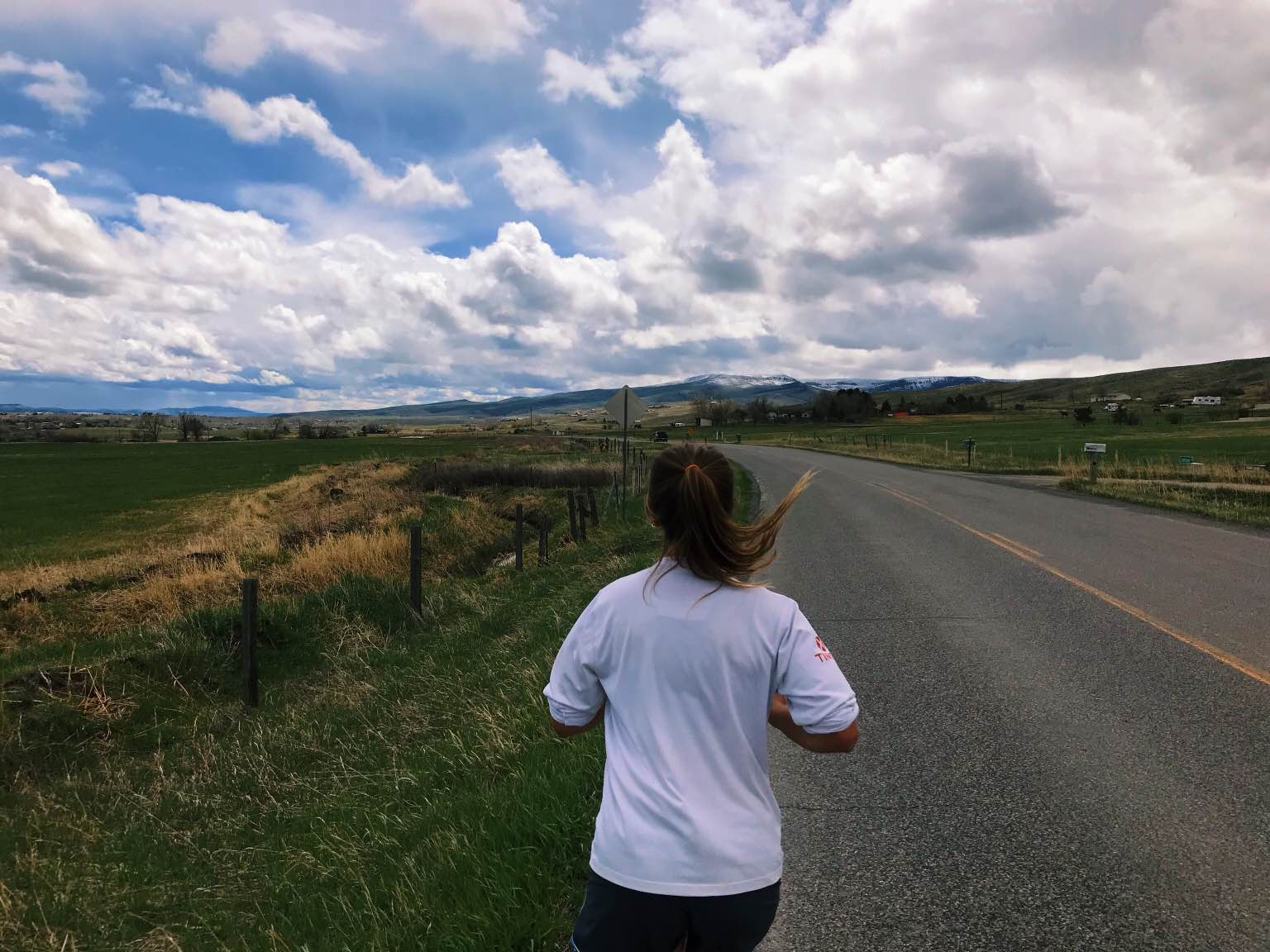 girl runs down a paved road with green fields on either side and dramatic clouds overhead