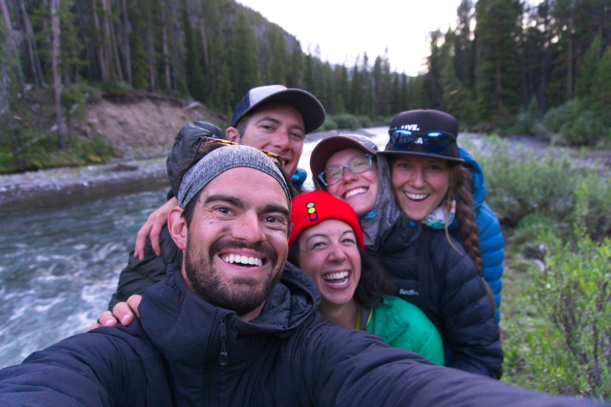 selfie photo of five smiling students on a cloudy day with a river in the background