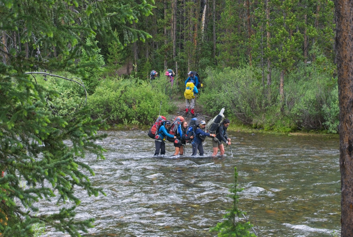 students walk down a trail to the river as other students wearing backpacks cross a river surrounded by thick forest