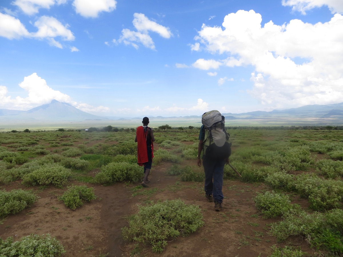 Two people, seen from behind, backpack through Maasai Land in East Africa with the slopes of Mt Kilimanjaro in the distance