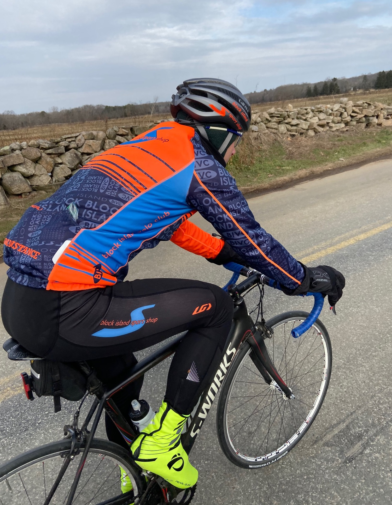 cyclist wearing blue and orange kit rides on a paved road alongside stonewall
