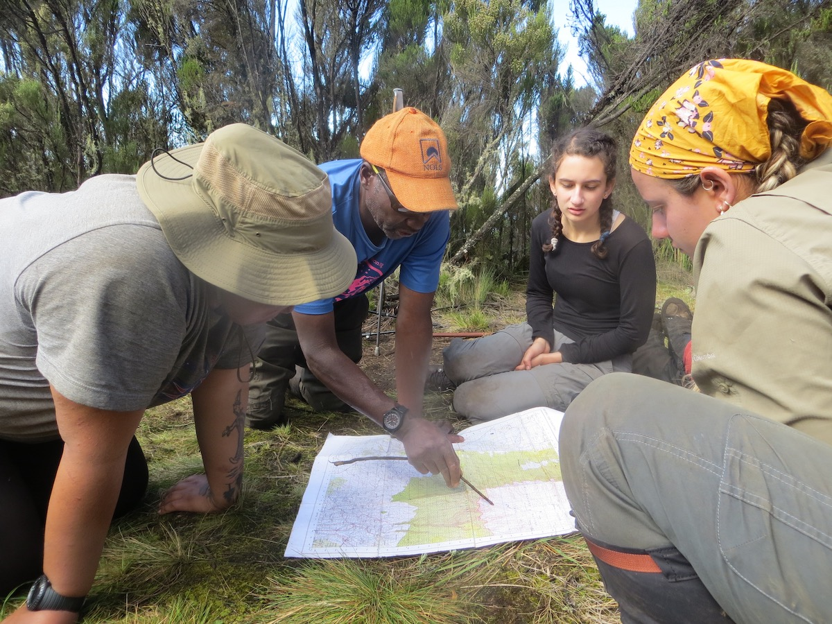 NOLS instructor teaches students how to read a topo map spread out on the ground in Tanzania