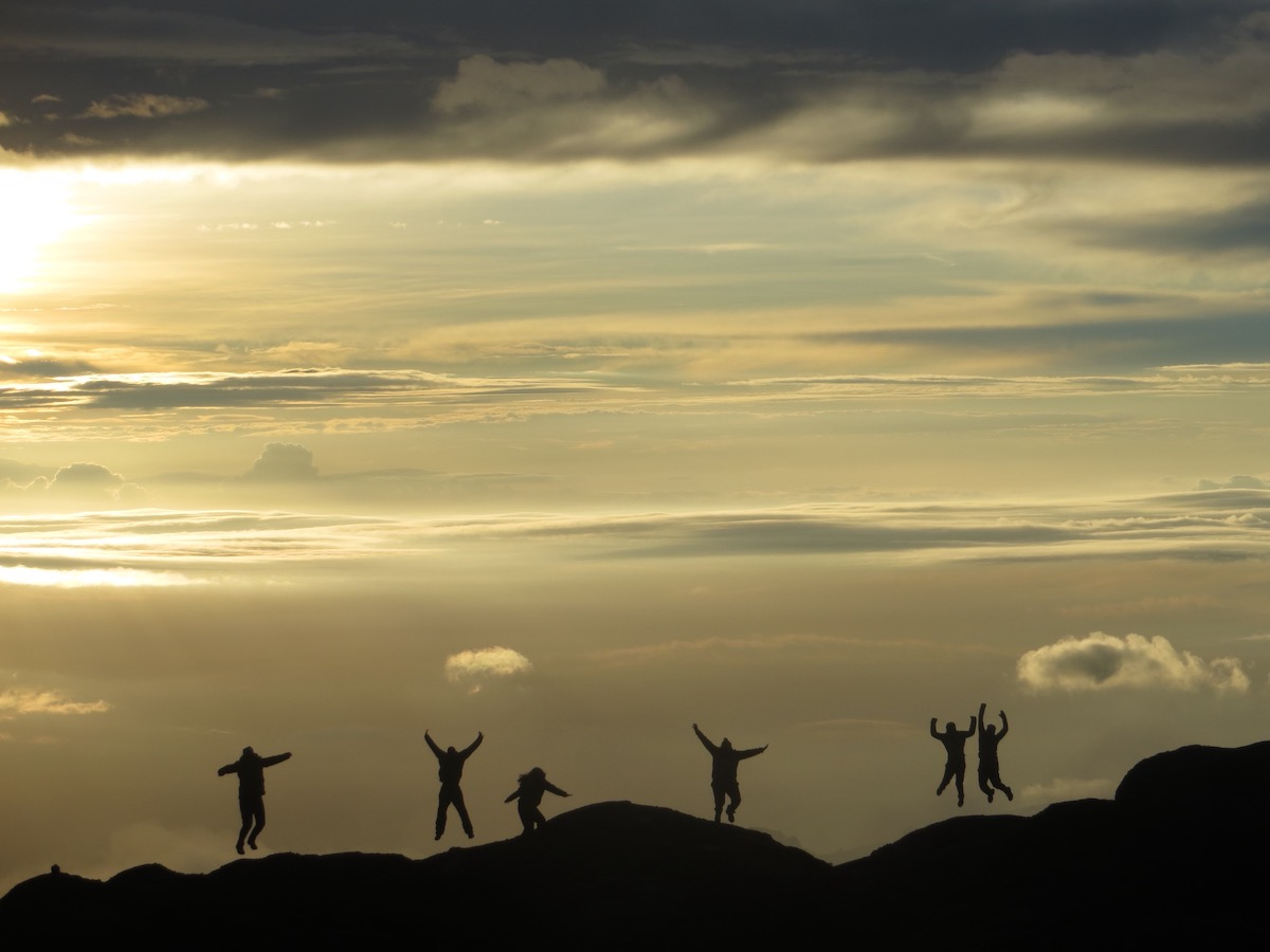 five silhouetted figures leap into the air on the top of a peak in Tanzania