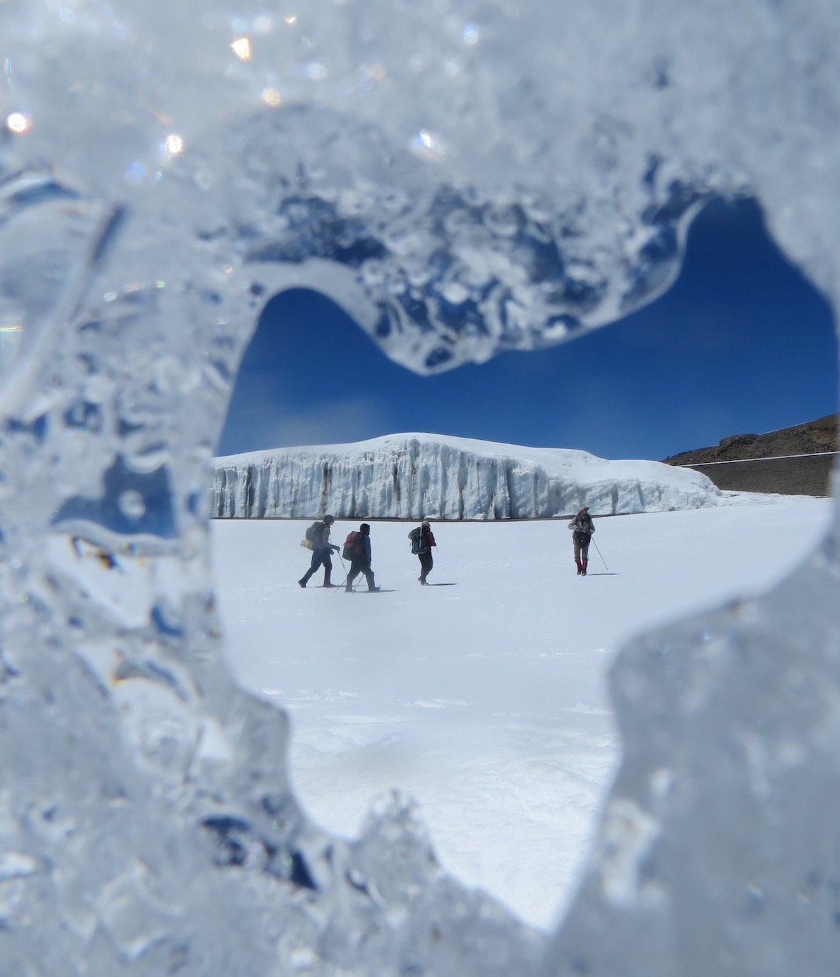 four students hike across a snowfield on Mt Kilimanjaro, as viewed through a crack in a melting glacier