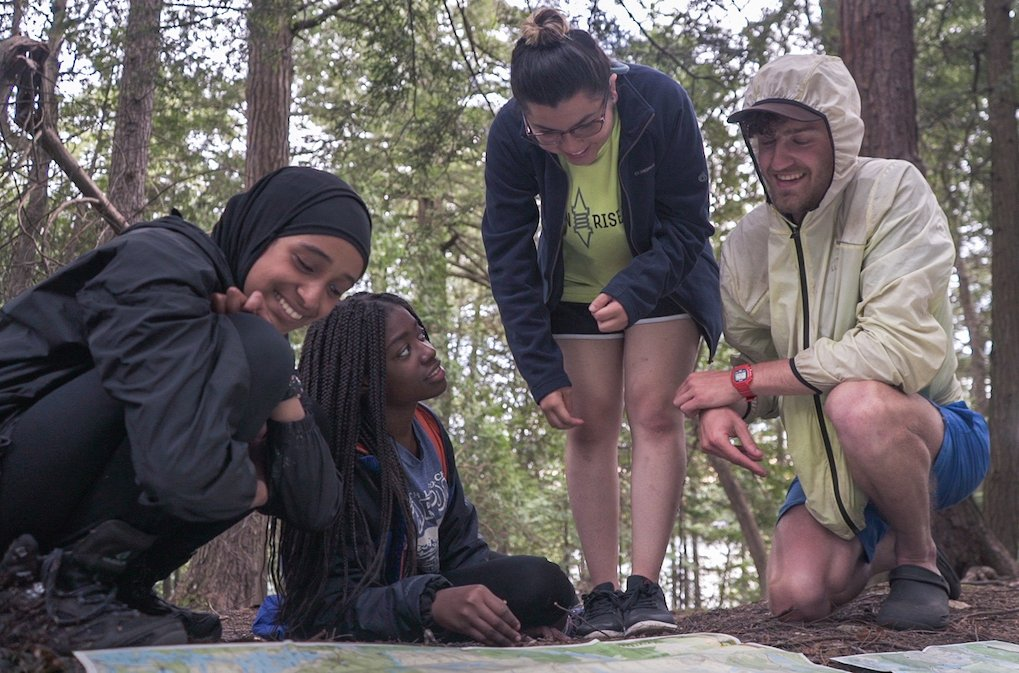four NOLS participants gather around to examine a map laid out on the forest floor