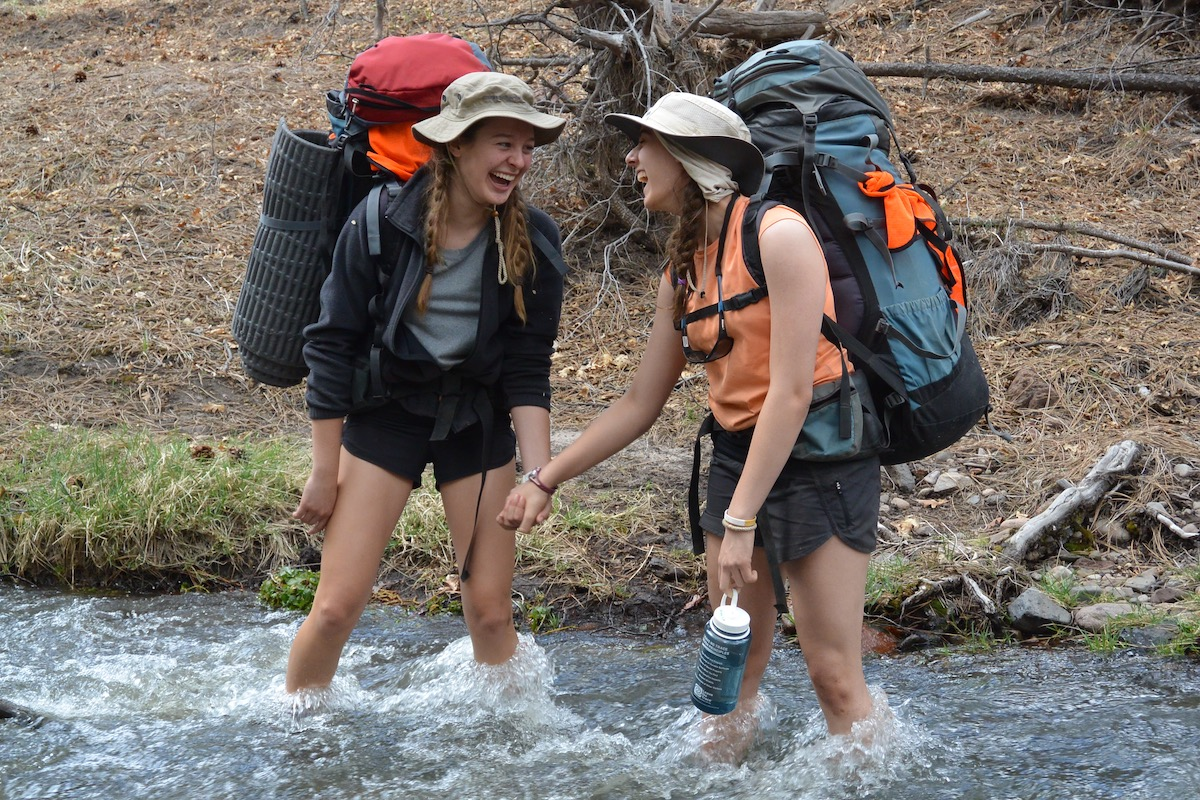 two smiling teenage girls wearing backpacks hold hands while crossing a river