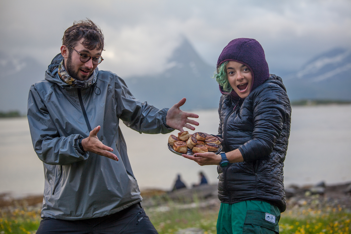 two people make goofy faces and show off a pan of cinnamon rolls in Scandinavia on a foggy morning