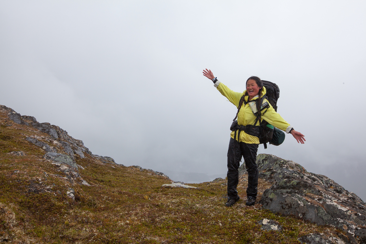 smiling woman with backpack stands on rocky ground and flings up her arms on a foggy day in the mountains
