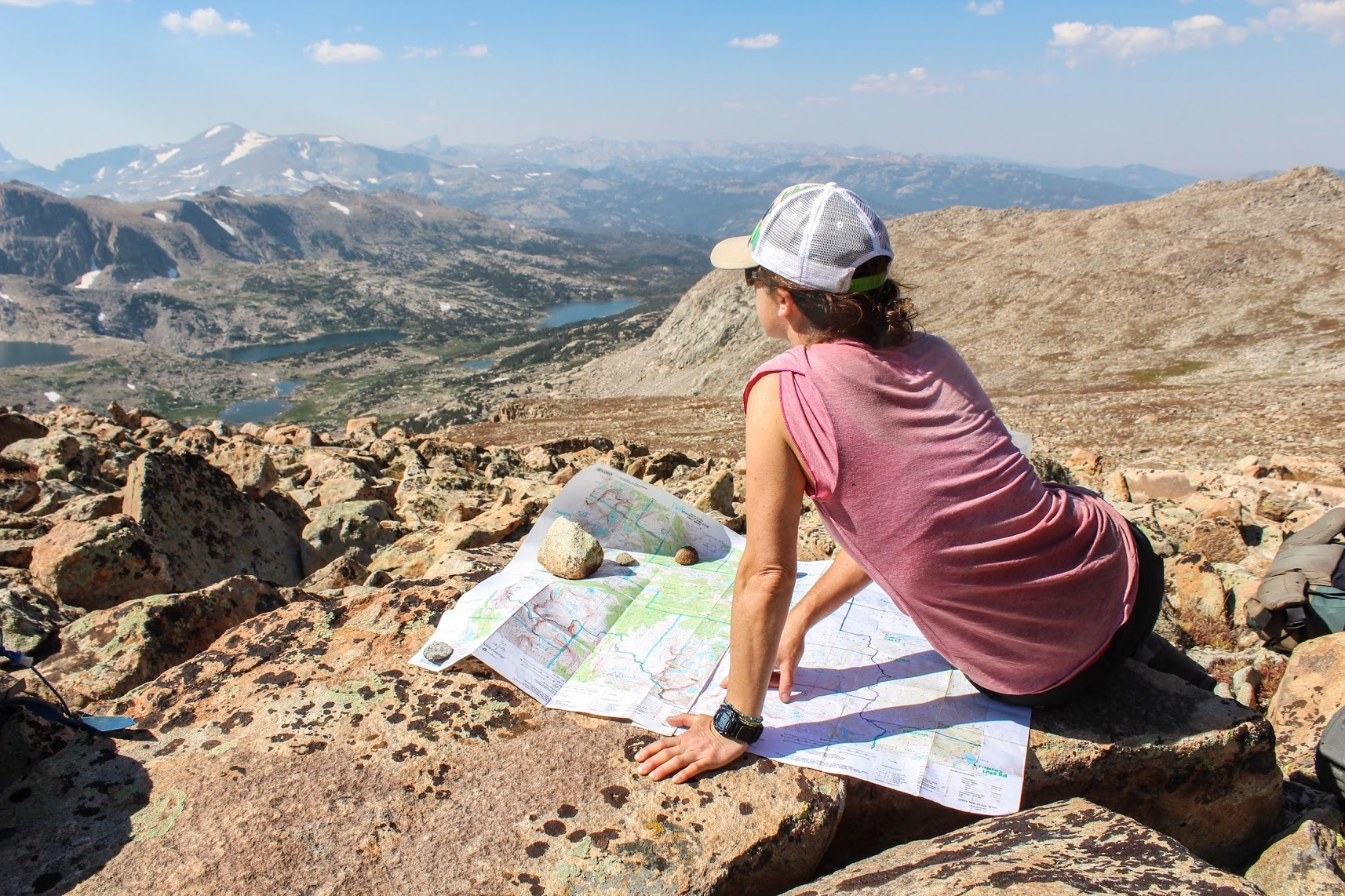 woman wearing baseball cap sits next to a map weighed down with rocks in the mountains