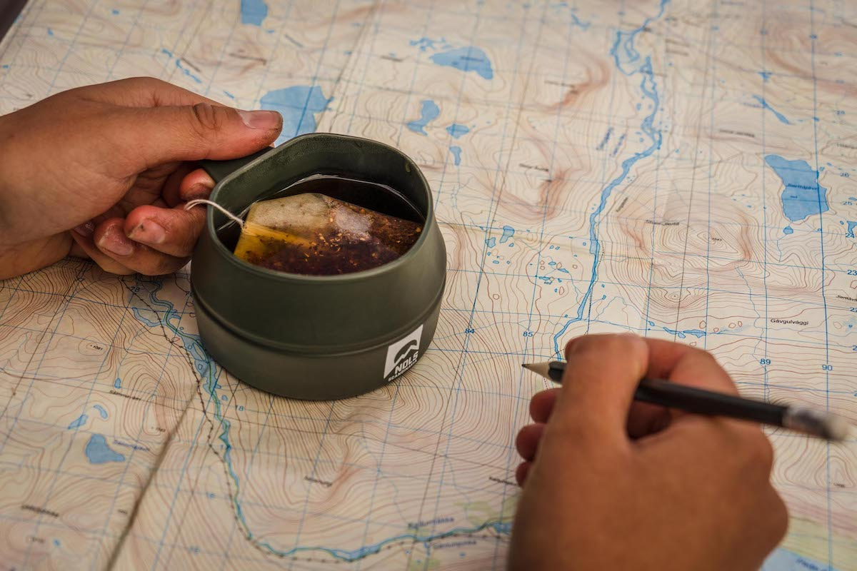 two hands on a topo map with the left hand holding a mug of tea and the right holding a pencil