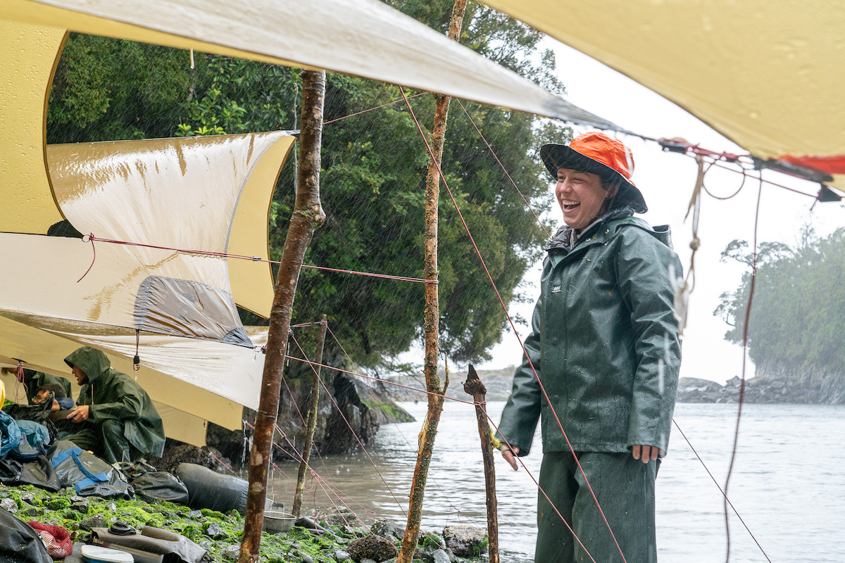 woman wearing orange hat and rain gear laughs while standing under a tarp near the water's edge in a rain storm