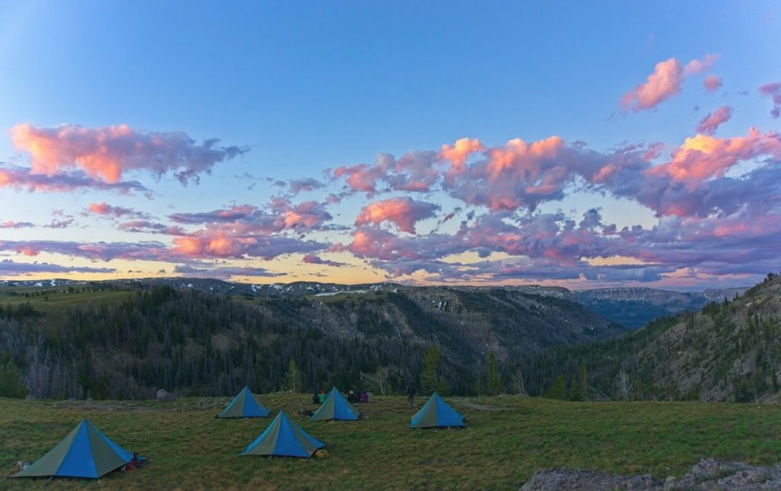 five blue and tan NOLS mega mid tents set up in a green meadow in the mountains at sunset