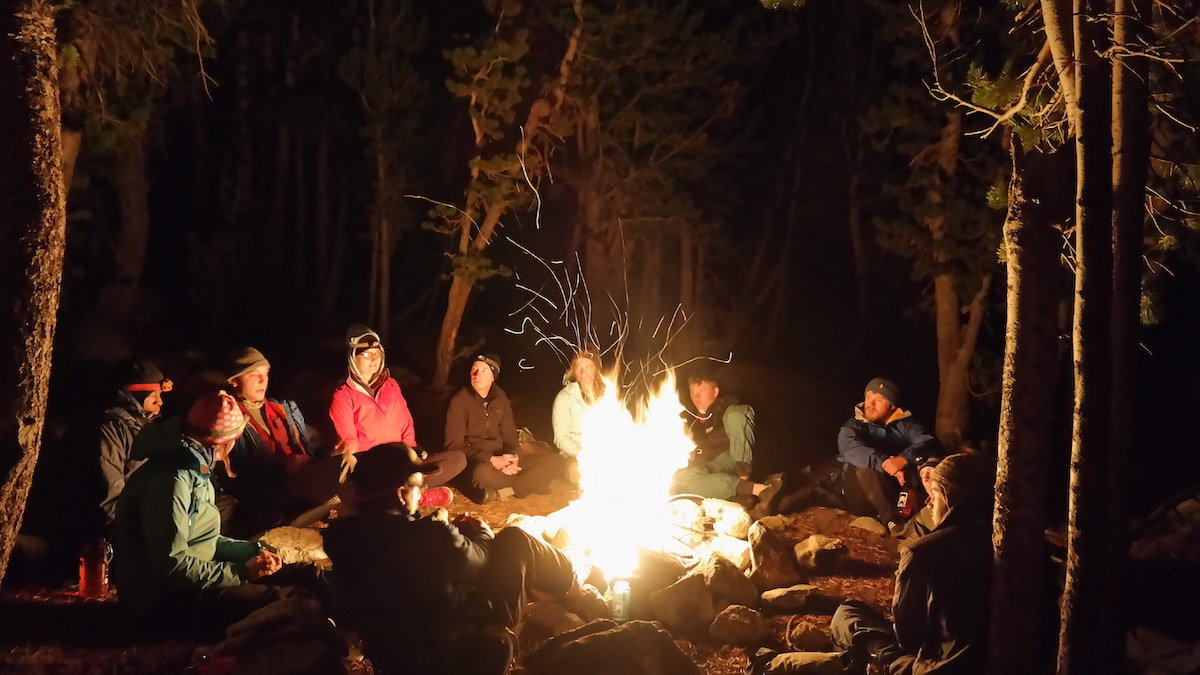 group of NOLS participants sit around an evening campfire in the woods