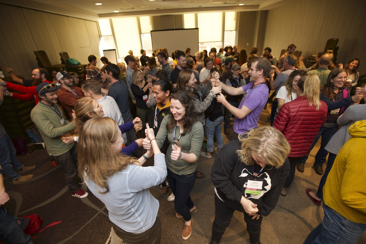smiling WRMC attendees in a crowded room stand to participate in a group activity