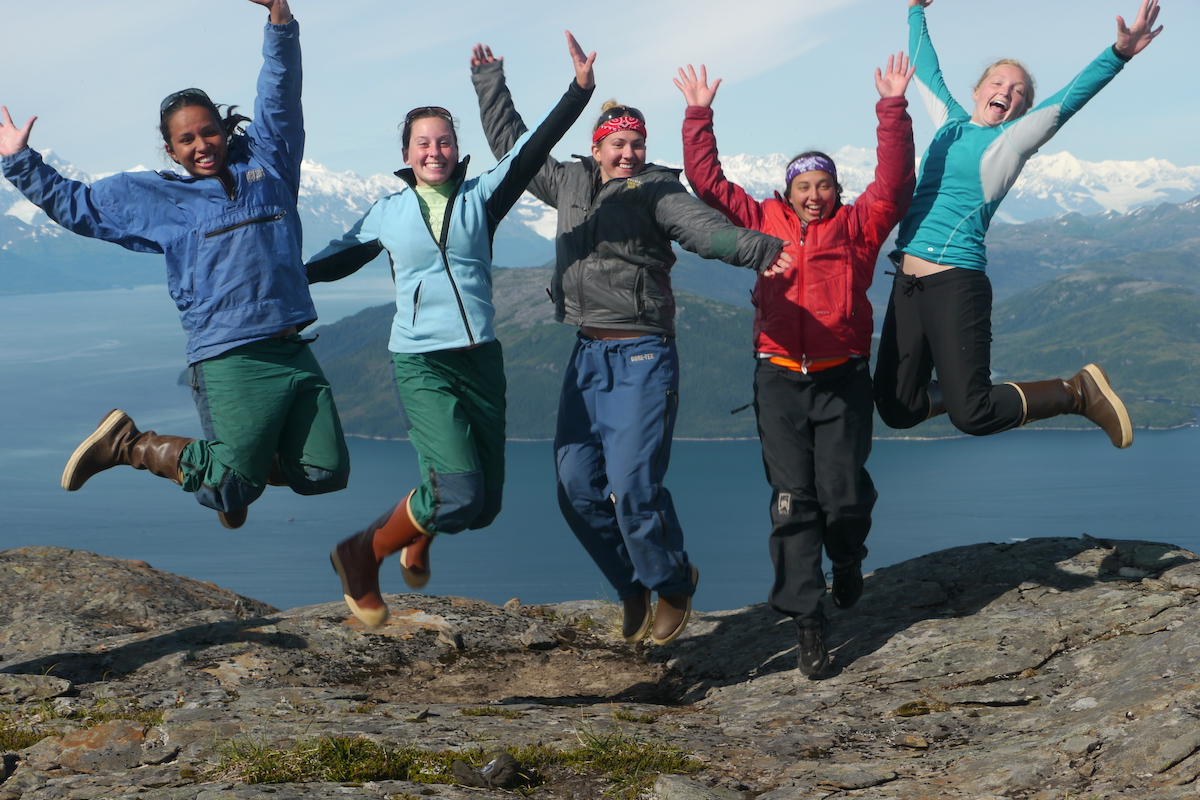 five female NOLS students smile and leap into the air on a rocky ledge in Alaska