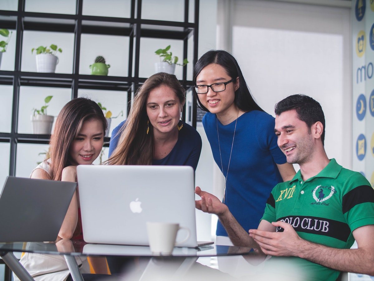 four smiling people cluster around an Apple laptop in an office
