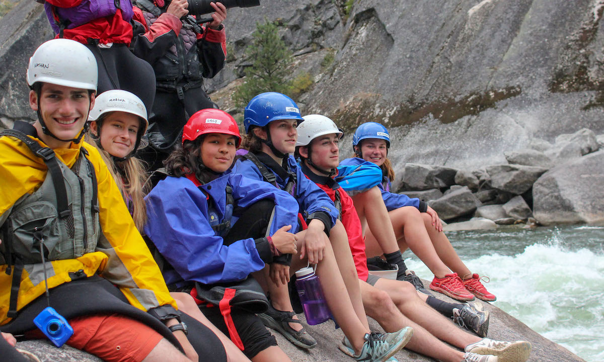six teenage NOLS students sit on a rock wearing helmets on a Salmon River rafting course