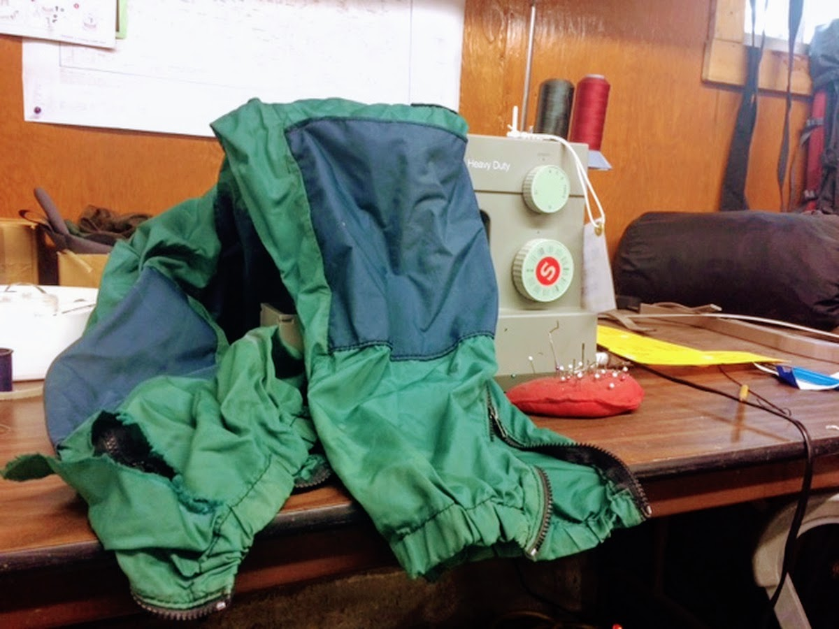 green and blue NOLS windpants draped over a sewing machine awaiting repair