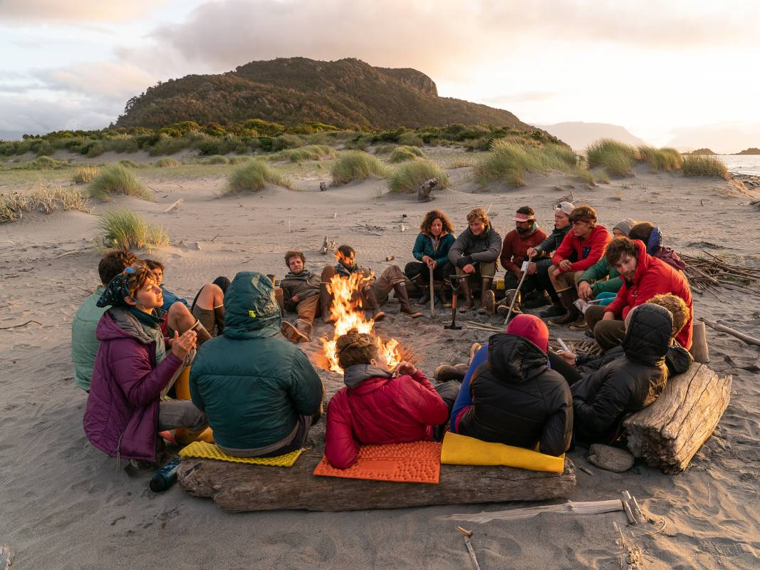 Group sits in a circle around a fire on a sandy beach