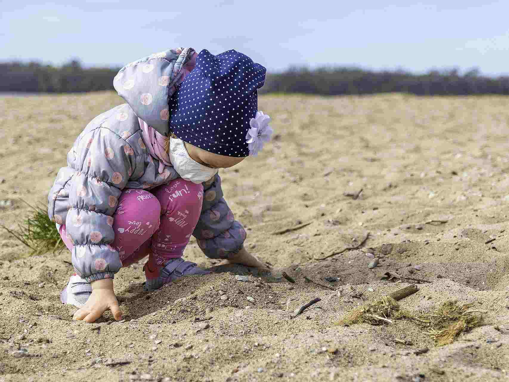 Toddler bends over the sand while wearing a hat and face covering