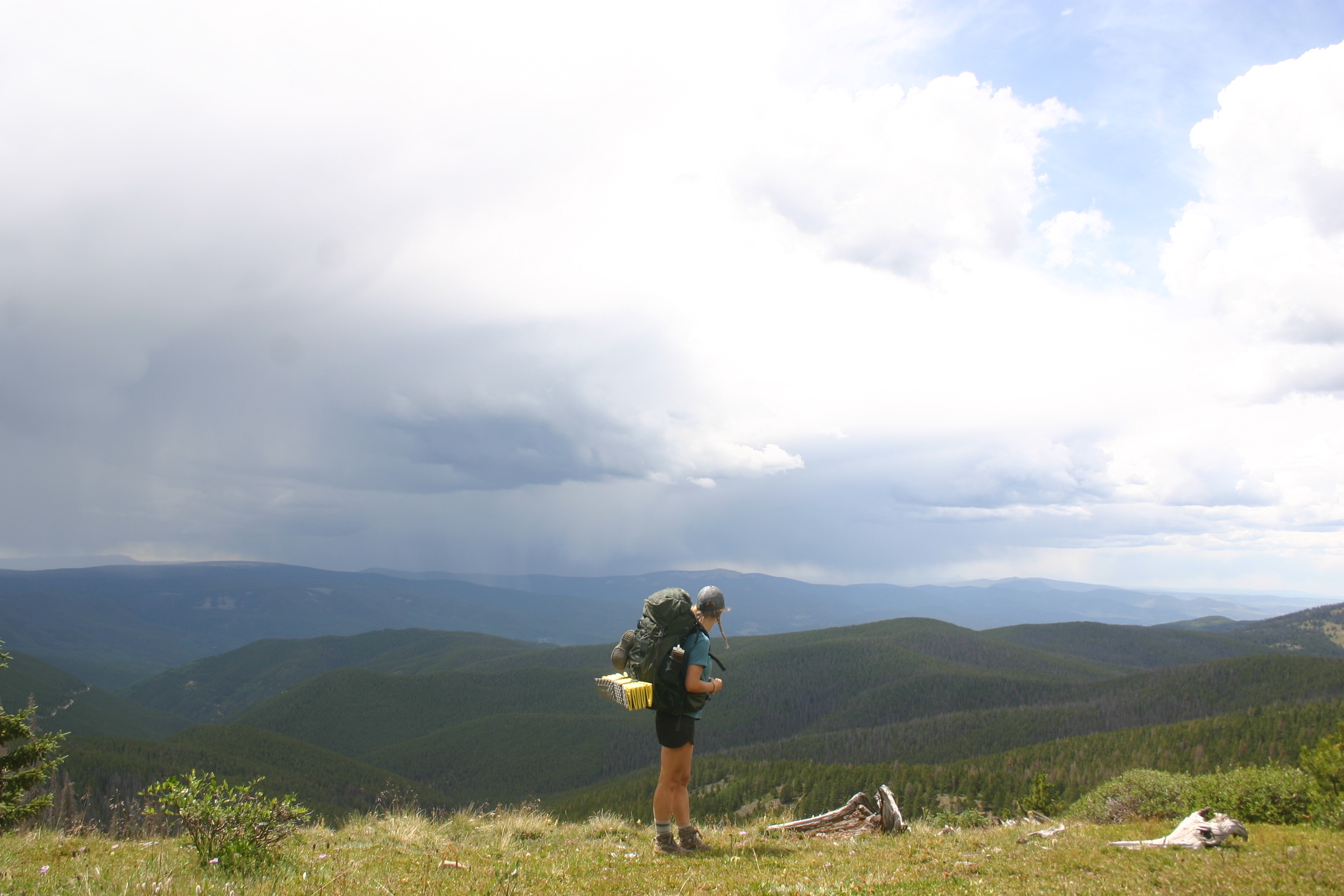 Kenna Kuhn overlooks a mountain valley while backpacking