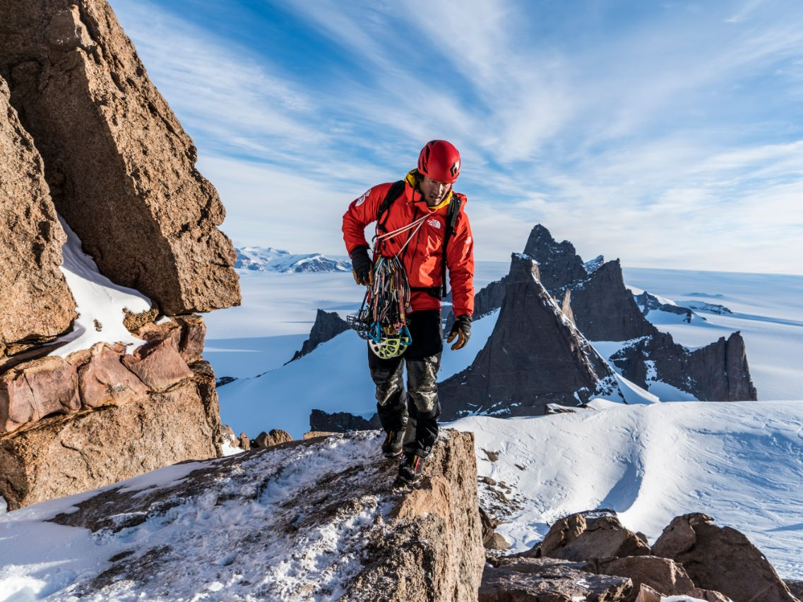 Jimmy Chin walks on a snowy rock ridge with a climbing rack of gear and a red jacket and helmet