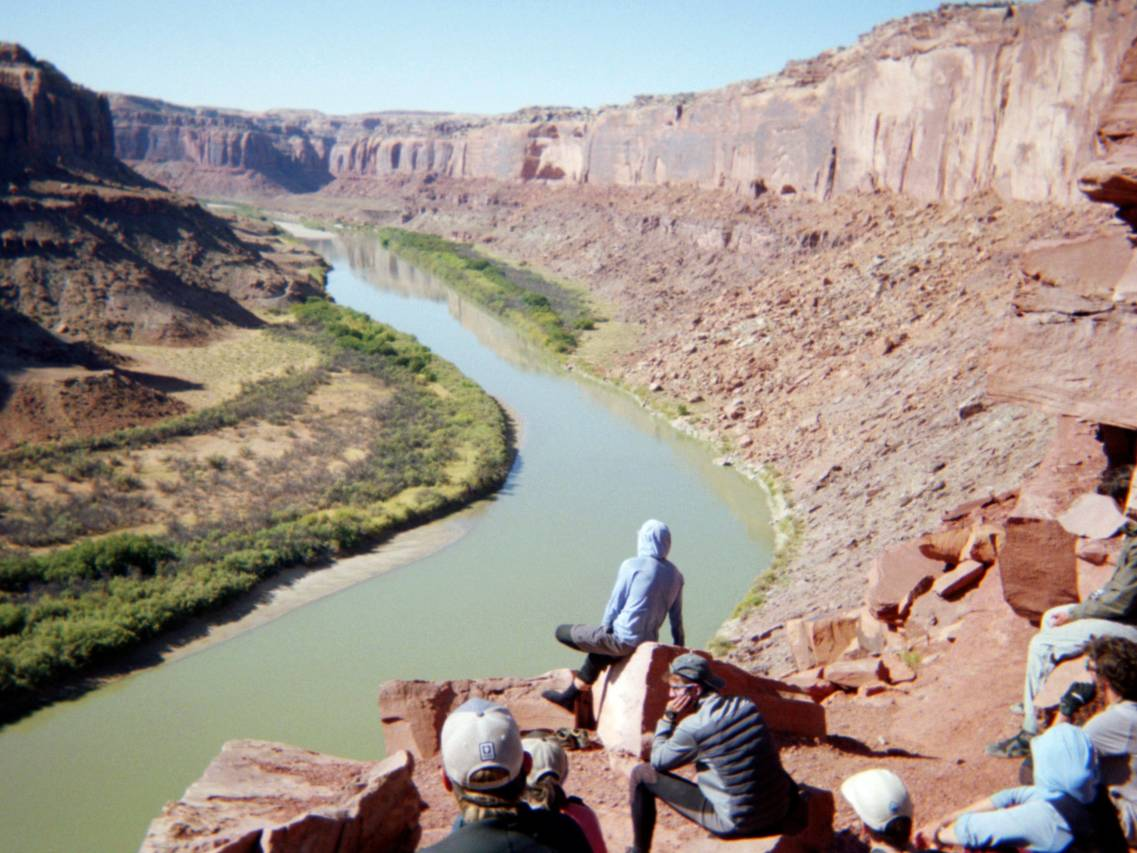 NOLS students overlook a river in a desert canyon