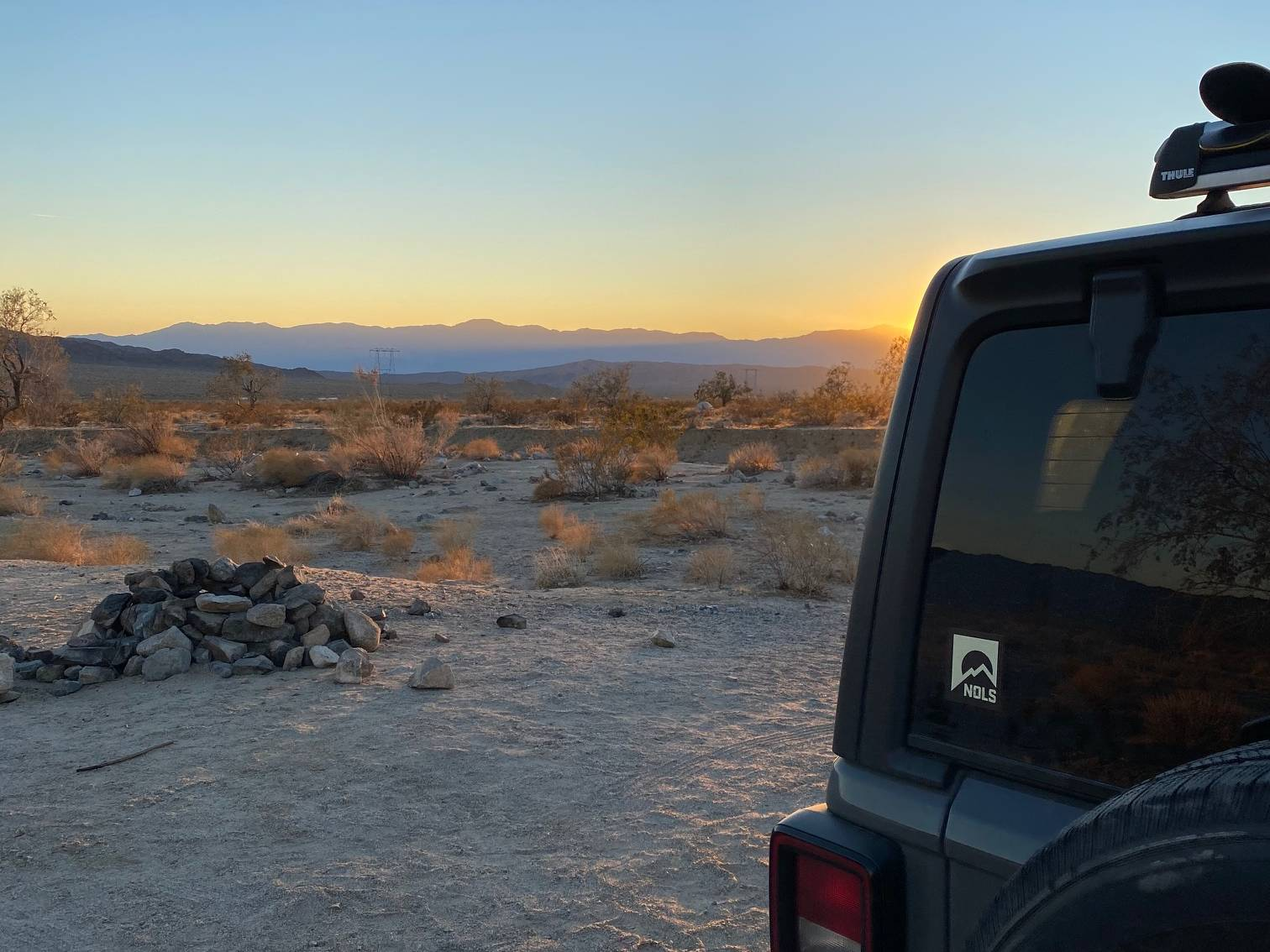 Back of a jeep in the desert at sunset
