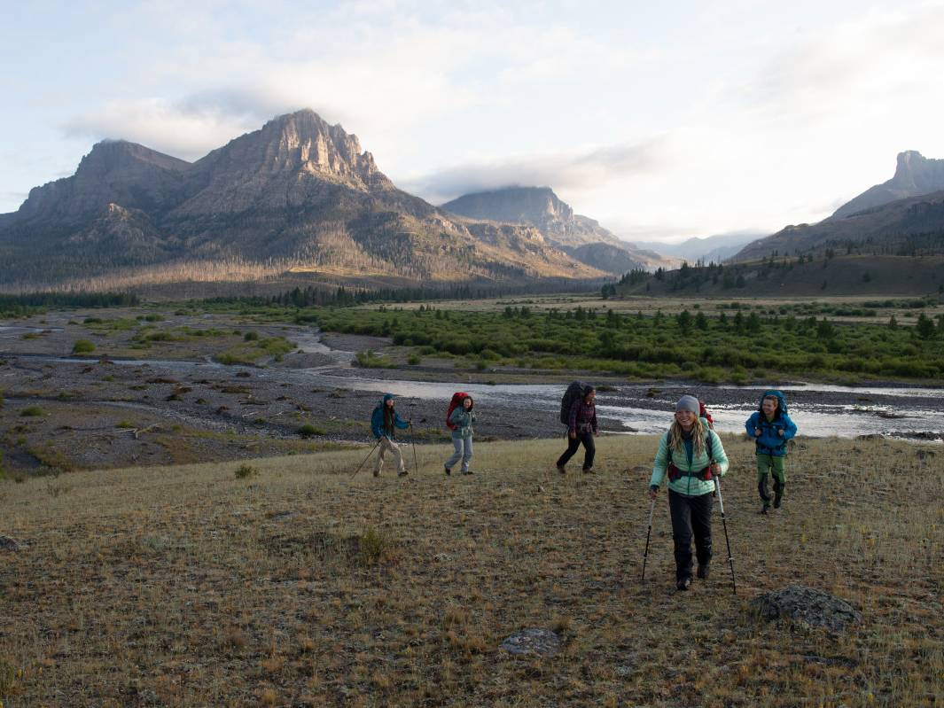 Hikers cross a mountain meadow