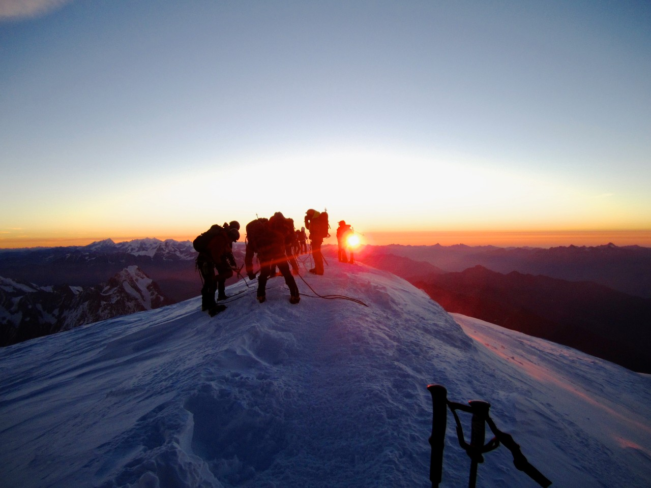 Mountaineers on a summit ridge with sunset in the background
