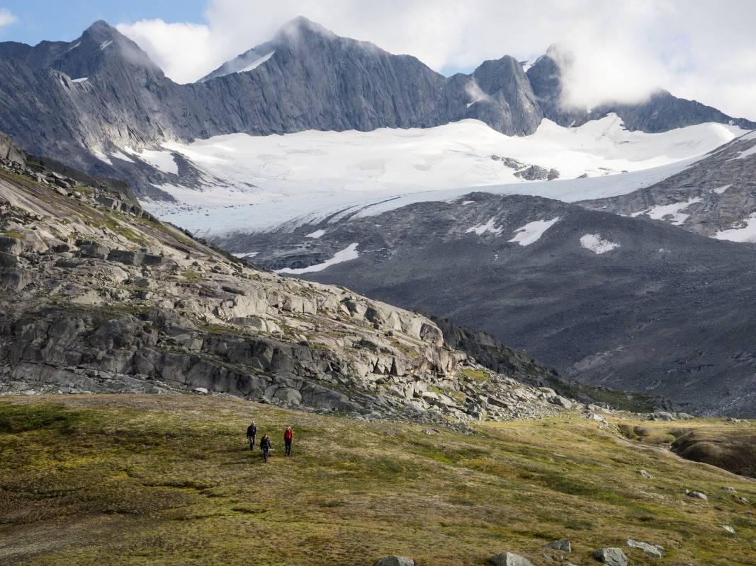 Hikers cross an alpine meadow in a stunning mountain landscape