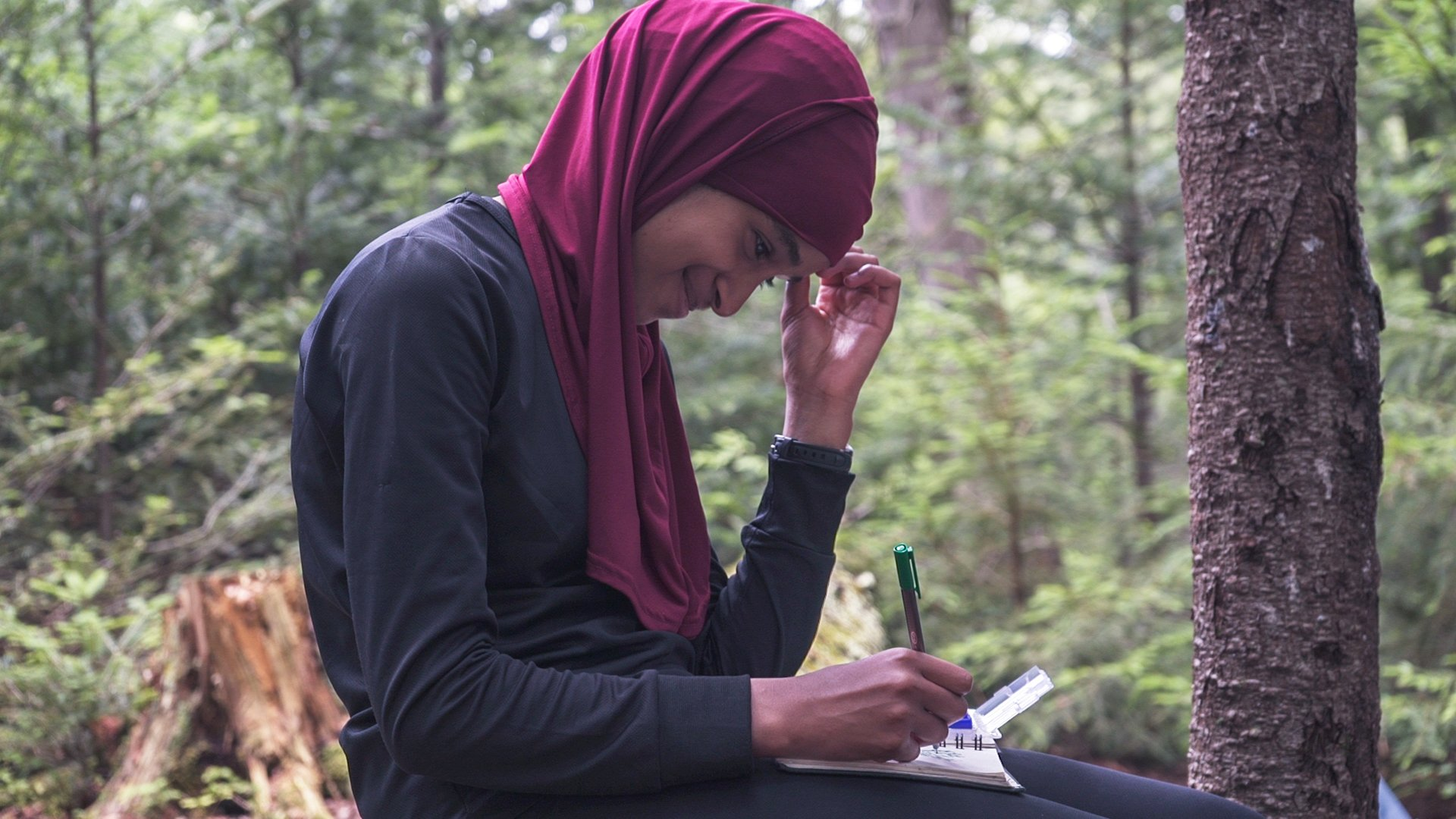 A student smiles while writing in the Adirondacks