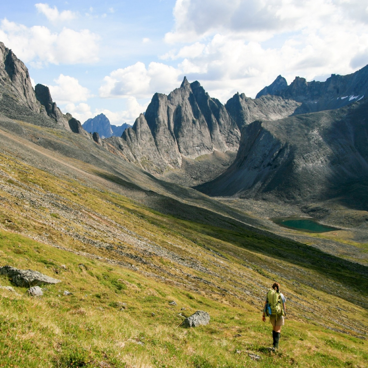 A hiker walks across the side of a valley with steep mountains in the background