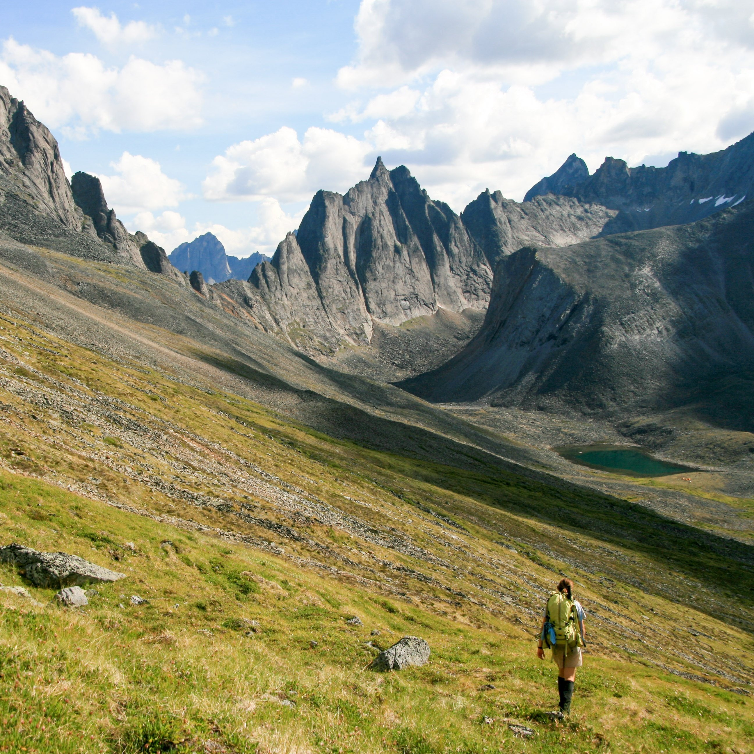 Backpacker hikes through grassy foothills in the Yukon with high, steep peaks in the background