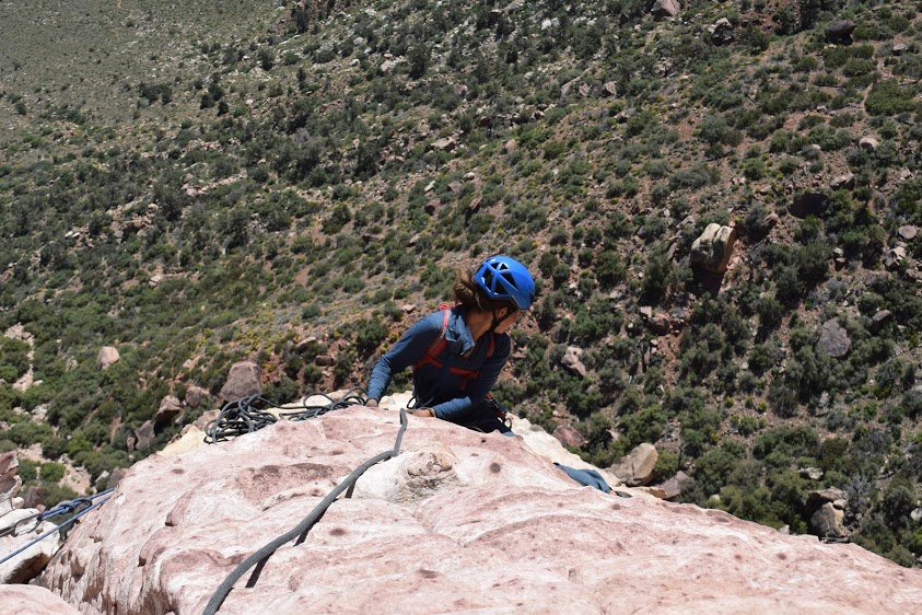 A climber wearing blue helmet glances below her from high on a rock wall