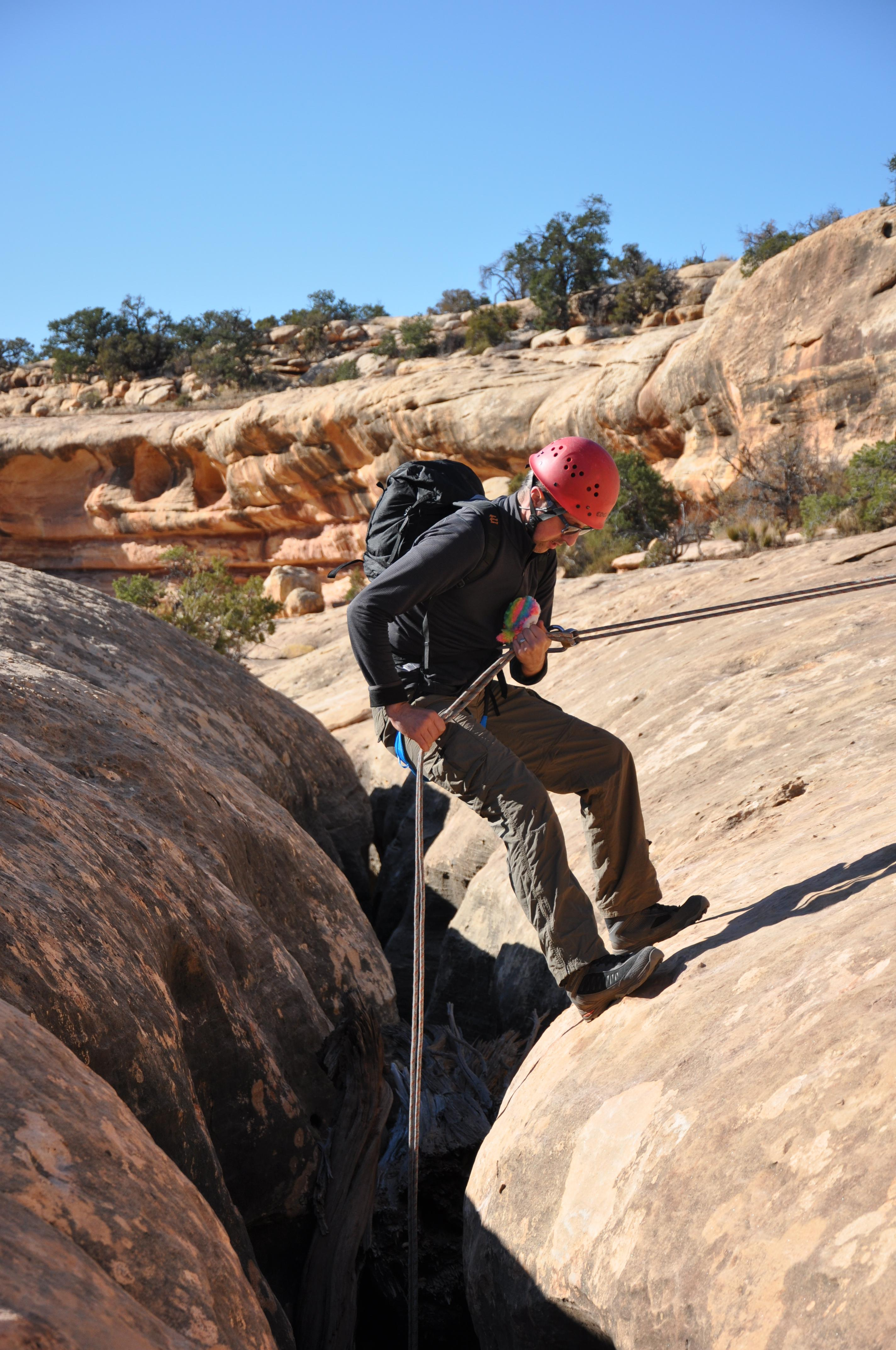 NOLS student wearing red helmet rappels in Utah's canyonlands