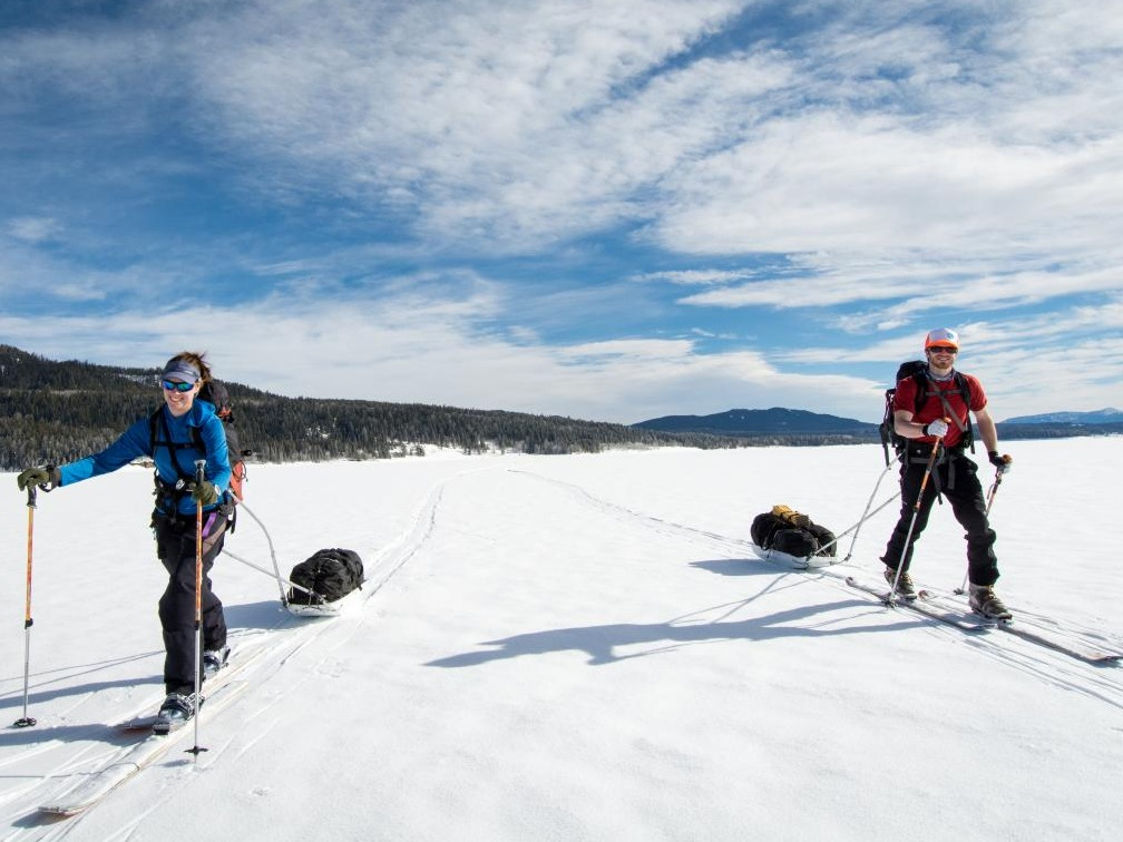 Two smiling people ski touring and pulling sleds across a snowfield