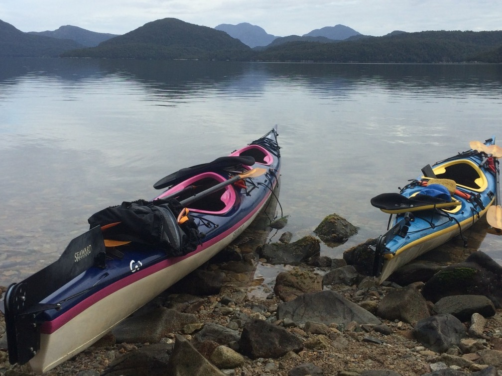 Two sea kayaks beached on a rocky shore