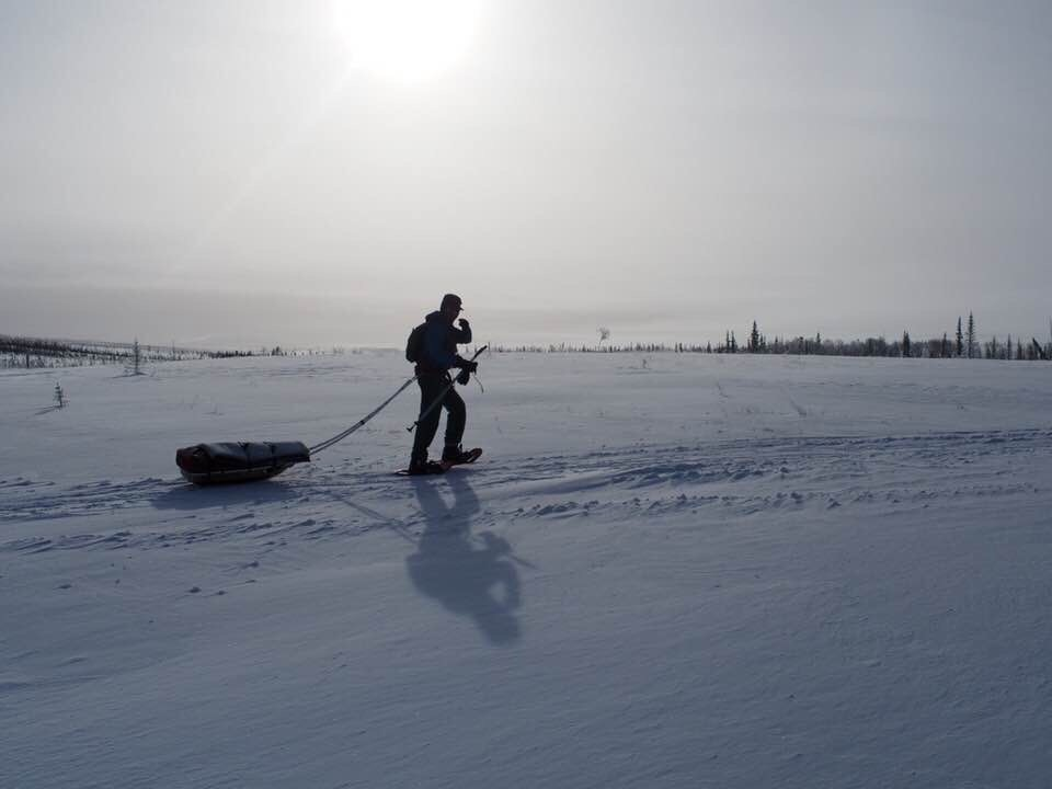 hiker pulling a sled treks across the snow in Alaska with sun shining through overcast sky