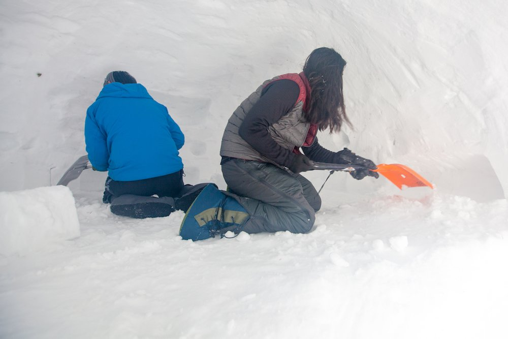 Two people work with shovels to scoop out the snow from the interior of a quinzhee