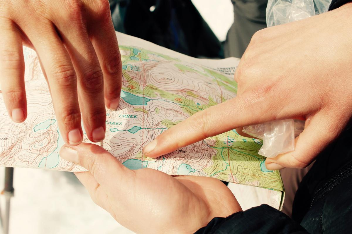 three hands holding and pointing at a topo map