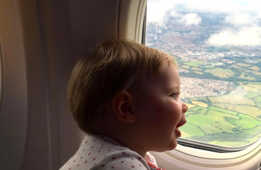 Baby smiles and looks out an airplane window at patchwork of green fields