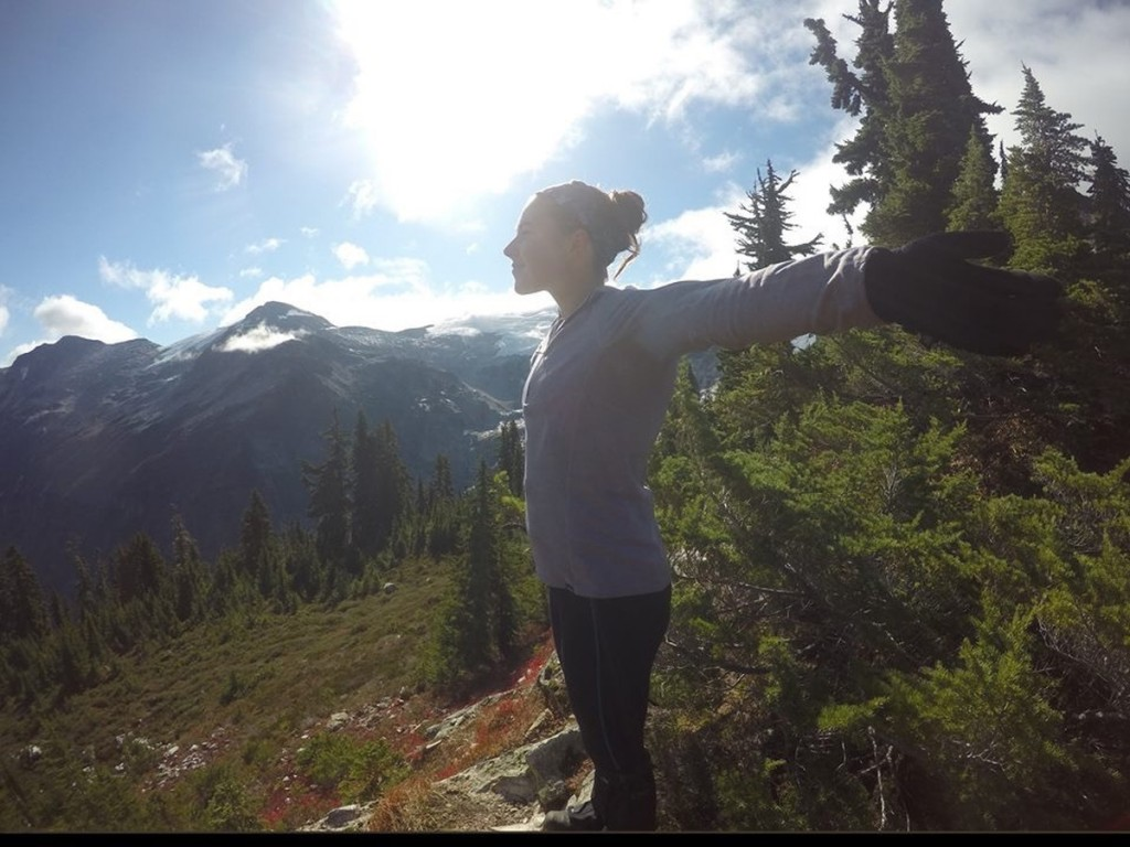 NOLS participant stretches her arms wide, enjoying sunshine in the mountains