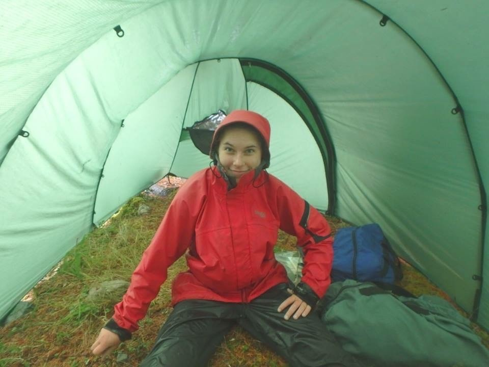 smiling NOLS student wearing rain gear sits in a tent