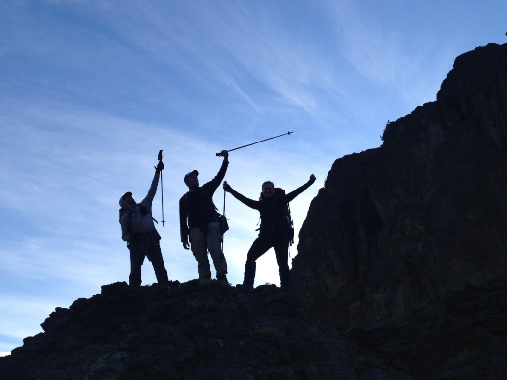Three backpackers silhouetted on a ridge